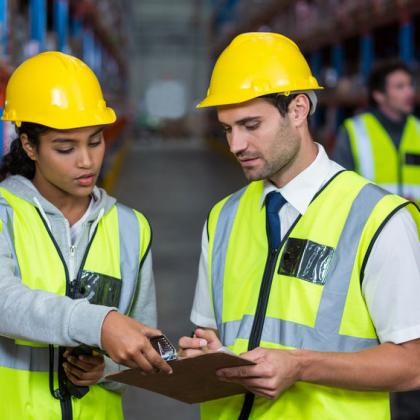 man and woman working together wearing construction west and helmet