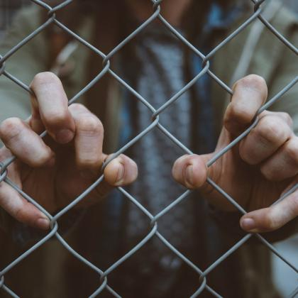 person grabbing onto fence with both hands with a blurred background