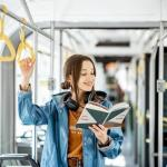 young woman reading on public transportation