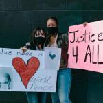 Two Women in Masks Holding Signs